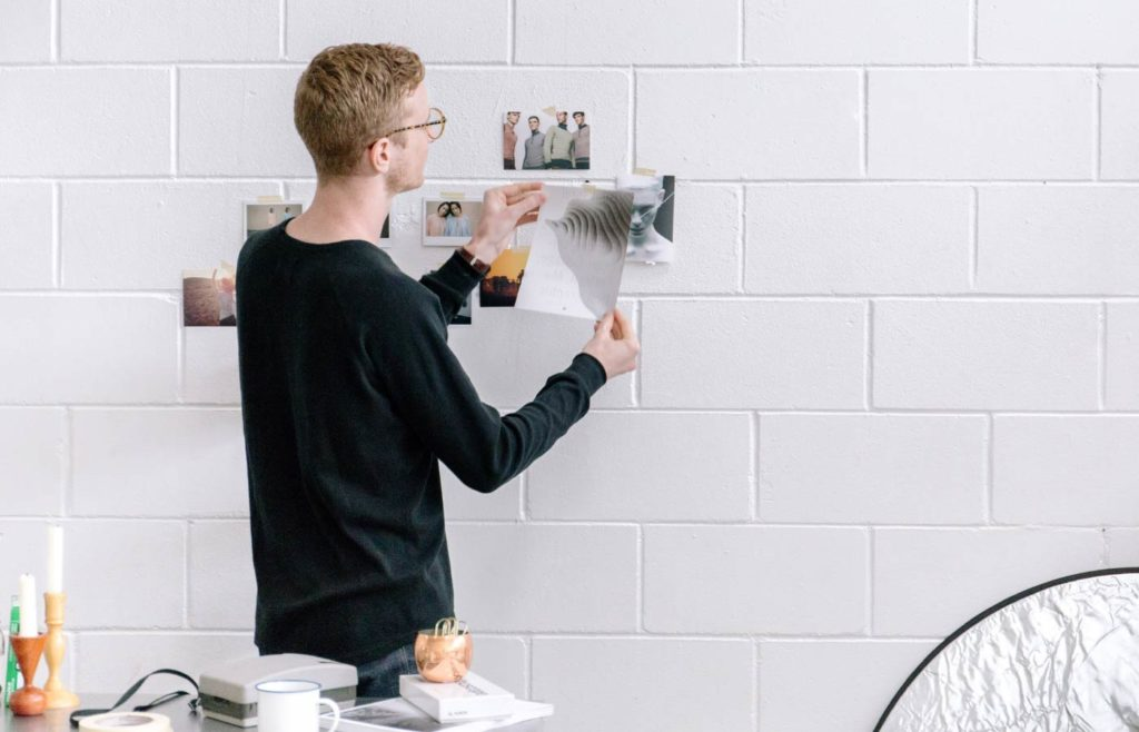 Man hanging pictures on a white brick wall